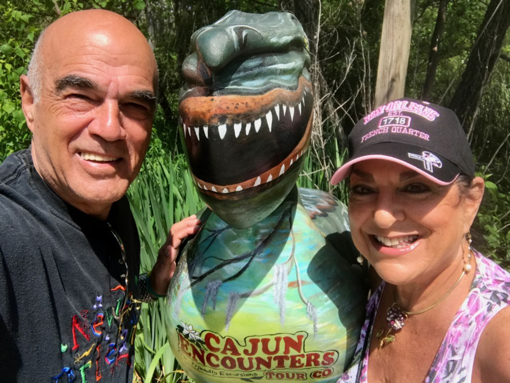 Bald man in black t-shirt (Steve) and woman with black and pink hat with an green alligator sculpture