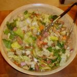 A large light wood salad bowl filled with greens, ham, cheese, tomatoes and carrots.
