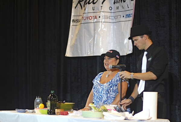 A man and woman adjusting a microphone at a cooking demo