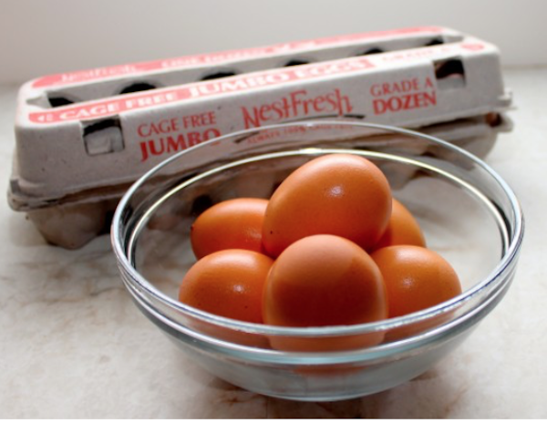 An empty cardboard egg carton with a glass bowl filled with brown eggs on a white marble counter