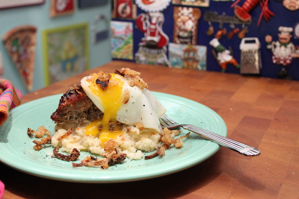 An aqua plate topped with mashed potatoes, meatloaf and a runny fried egg with a fork on the side sitting on a butcher block.