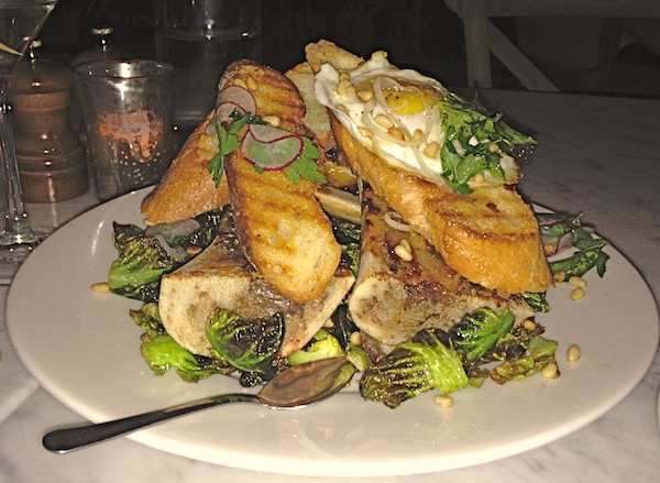 A white plate mounded high with roasted marrow bones, greens and toasted baguette slices.