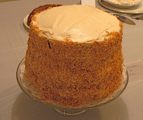 A very tall cake with toasted coconut on the outside sitting on a cake stand.