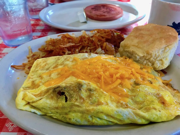 Western Omelet with crispy, crunchy Hash Browns and a great big fluffy biscuit on a white plate.