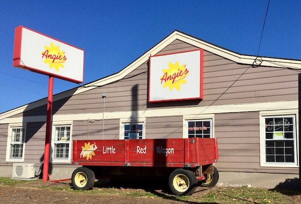 The outside of a restaurant with a large red wagon in front
