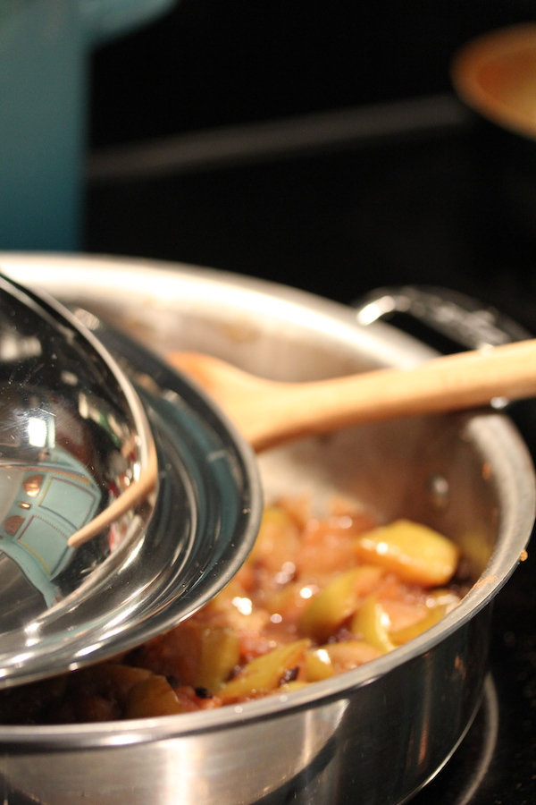 A stainless steel pan filled with apple compote and a wooden spoon with the lid partially covering pan