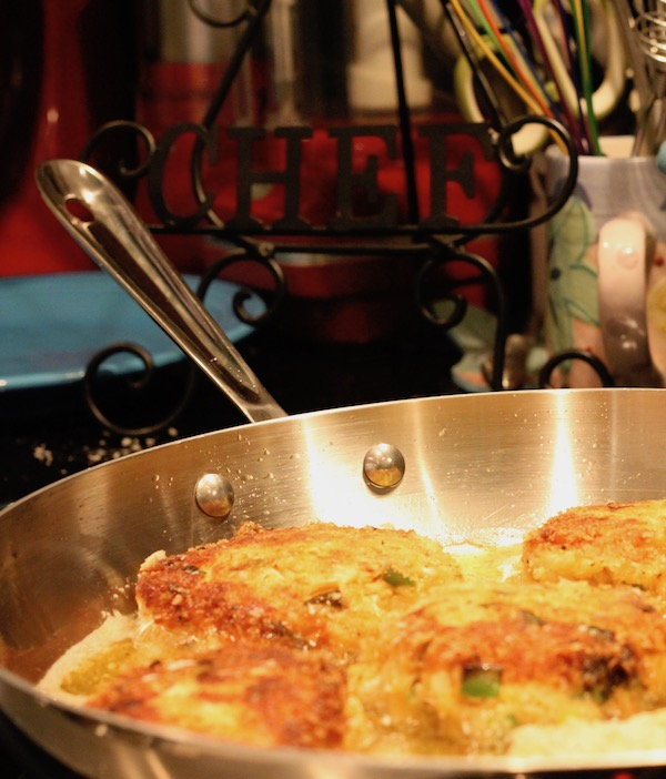 A sauté pan with Golden Brown Red Pepper Crab Cakes Frying and utensils in the background