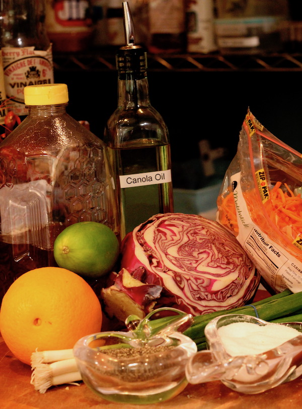 Assorted ingredients on a butcher block red cabbage, shredded carrots, scallions, and orange, a lime, bottles of honey and canola oil and a glass apple with cracked pepper and a glass pear filled with kosher salt