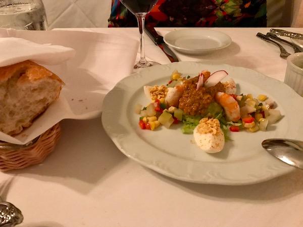Shrimp, assorted salad vegetables, deviled egg wedges and remoulade dressing on a white plate