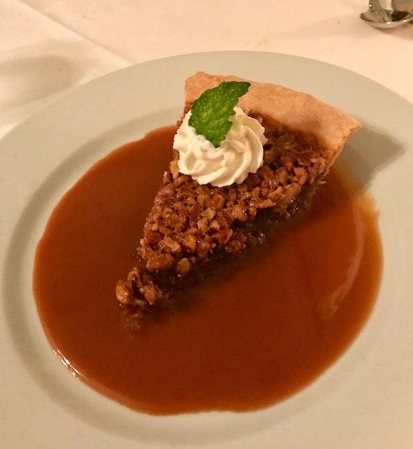 Luscious Pecan Pie with Caramel Sauce and a rosette of whipped cream and mint leaf on a white plate