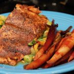 A medium blue dinner plate topped with Garam Masala Dusted Salmon on a Bed of Mango Tomatillo Salsa with Candied Ginger Carrots