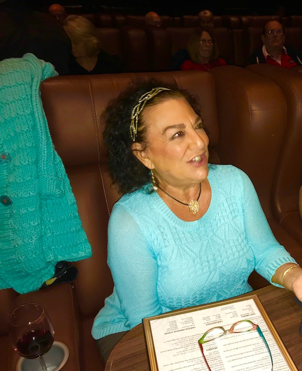 A woman in a turquoise sweater ordering dinner in a movie theater seat