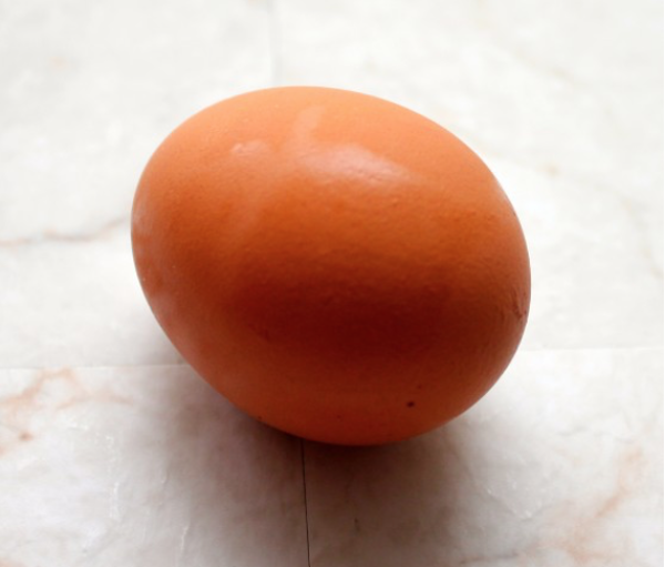 A single brown egg sitting on a white marble counter