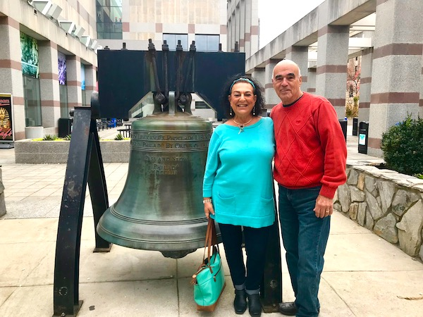 A woman in a turquoise sweater and a man in a red sweater standing next to a replica of the Liberty Bell