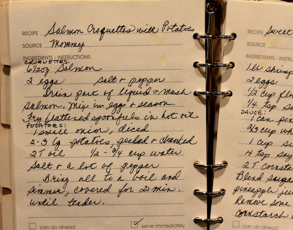A loose leaf book with yellowed pages and hand written recipes.