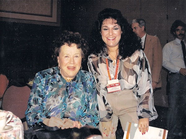 A woman with long dark hair standing next to Julia Child who is seated