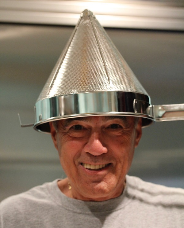A man smiling and holding a cone shaped strainer on his head
