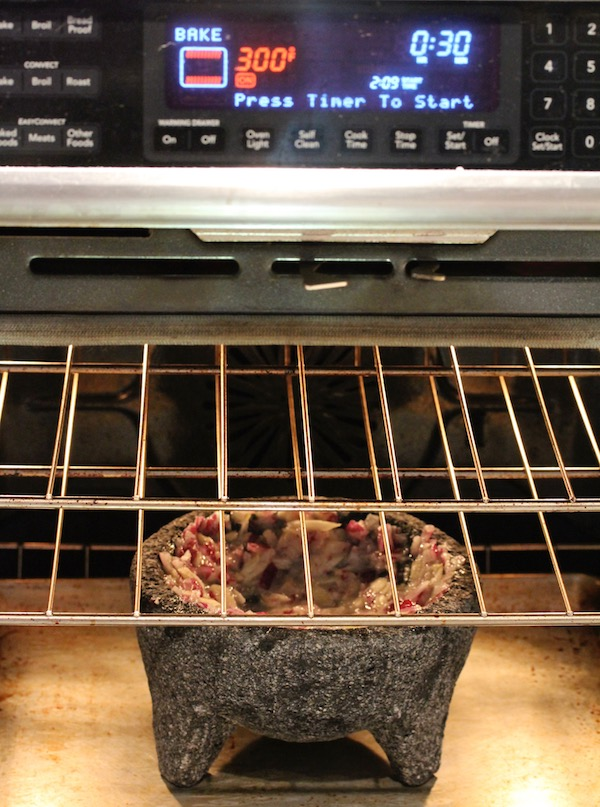 Looking into an oven with a lava rock mortar and pestle filled with chopped red onions on an oven rack.
