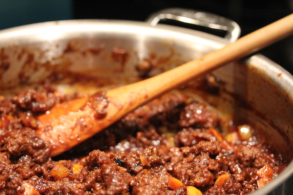 Steel pan with ground beef, bell peppers and tomatoes simmering with a wooden spoon on top