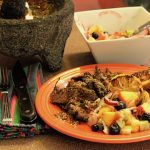 A molcajete with red salsa, an orange plate with Grilled Skirt Steak with Red Chimichurri and Peach Blueberry Tomatillo Relish and a square white bowl with the fruit relish and a spoon