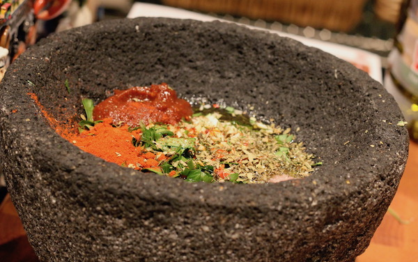 A large lava rock mortar filled with herbs, spices and tomato paste