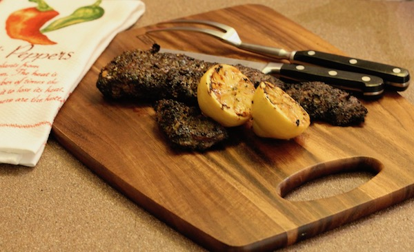 A cutting board with grilled skirt steak, two grilled lemon halves and a carving set.