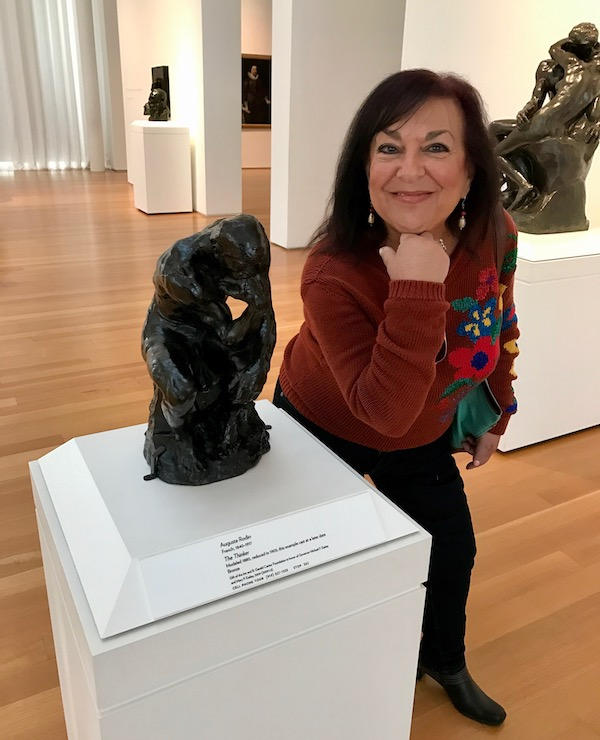 A woman posing as The Thinker next to the actual sculpture of The Thinker