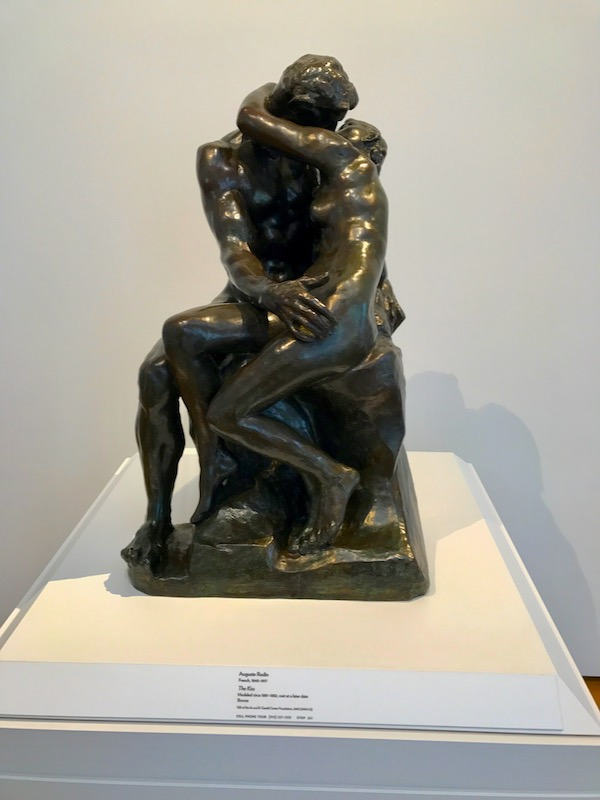 The Kiss by Rodin sculpture on a white pedestal