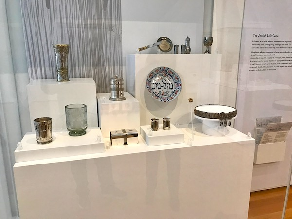 A very large glass case filled with judaica at a museum