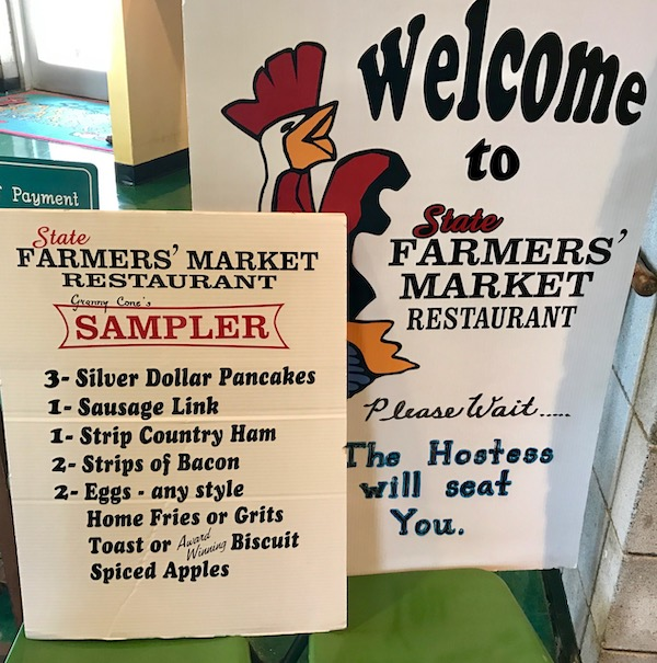 Large menu board welcoming you to the Farmers' Market Restaurant
