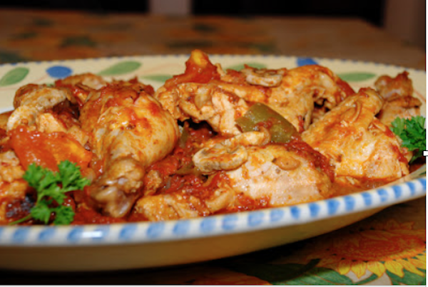 A painted oval ceramic platter filled with chicken cacciatore