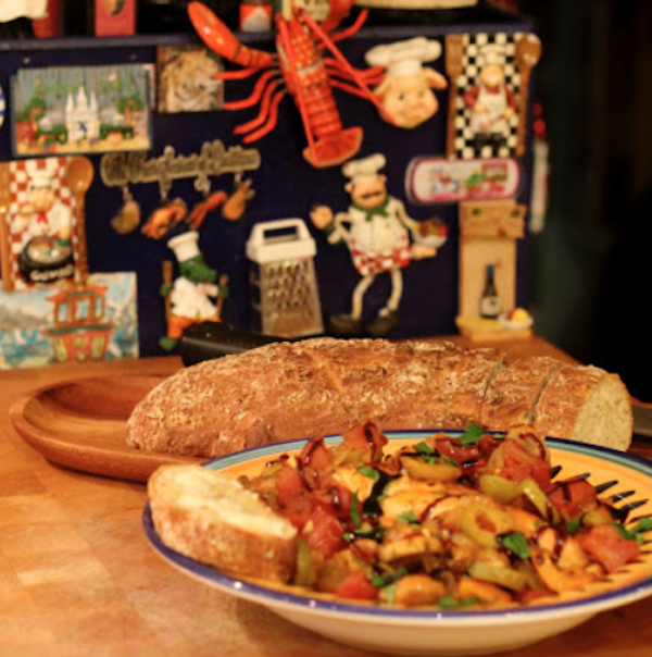 A yellow and blue dish filled with chicken cacciatore with a loaf of bread behind it.