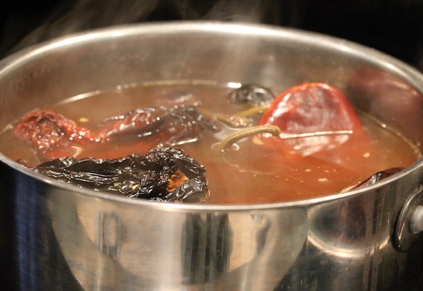 A steel stock pot filled with stock and assorted chiles for the Red Chile Short Rib Tacos.