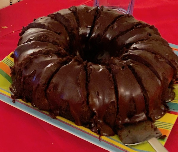 A frosted chocolate bundt cake on a striped plate