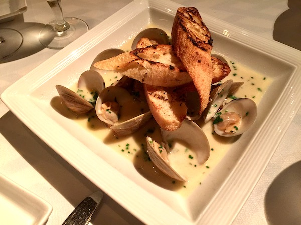 A large white square plate with clams and toasted baguette slices