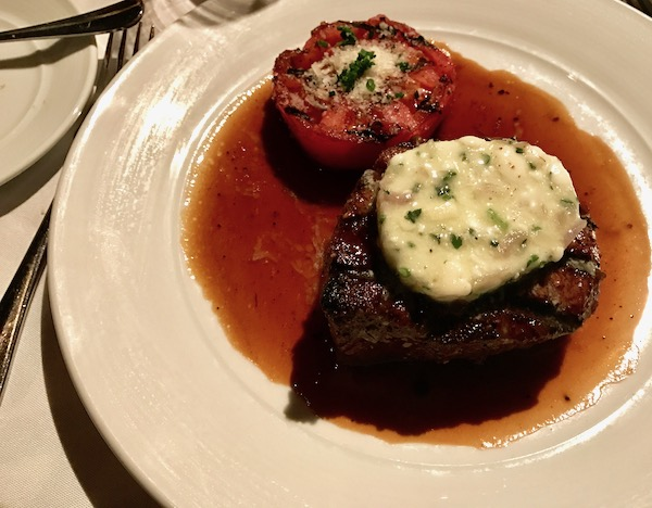 An ivory plate with Beef Tenderloin with Blue Cheese Butter and a half of a roasted tomato