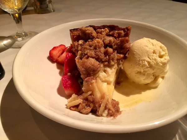 A wedge of Warm Sour Cream Apple Pie with a scoop of vanilla ice cream and sliced strawberries