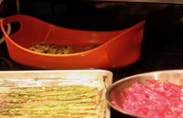 An orange baking dish with salmon, a foil lined sheet pan and part of a skillet with red cabbage.