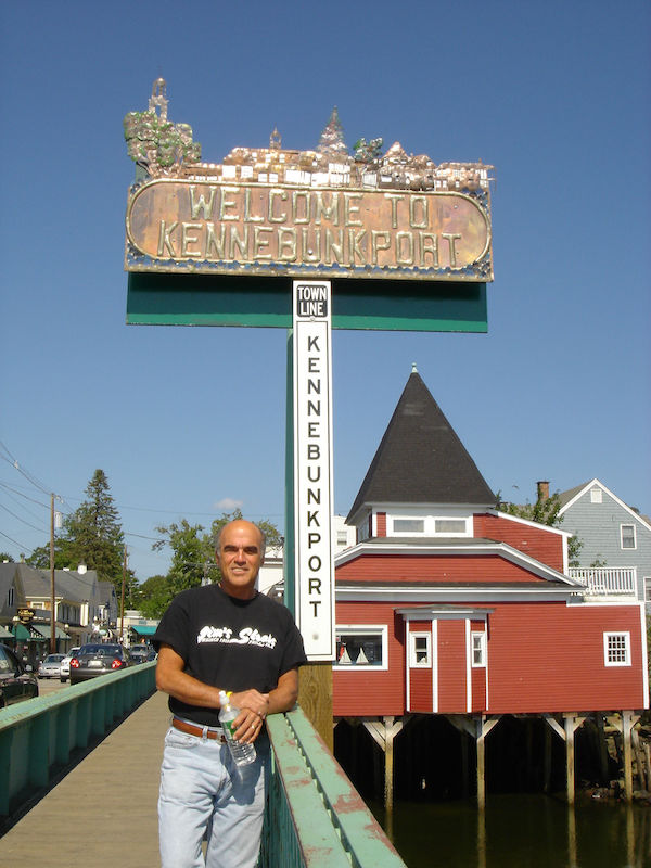 Steve by the Kennebunkport Maine sign with buildings in the background