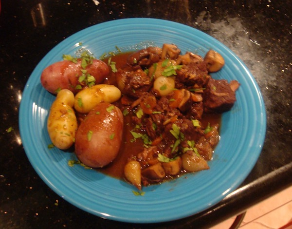 Peacock blue dinner plate with boiled fingerling and red skinned potatoes, wine braised beef, mushrooms and pearl onions