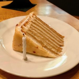 A slice of white layer cake with mocha colored frosting between the layers and a single candle on a white plate