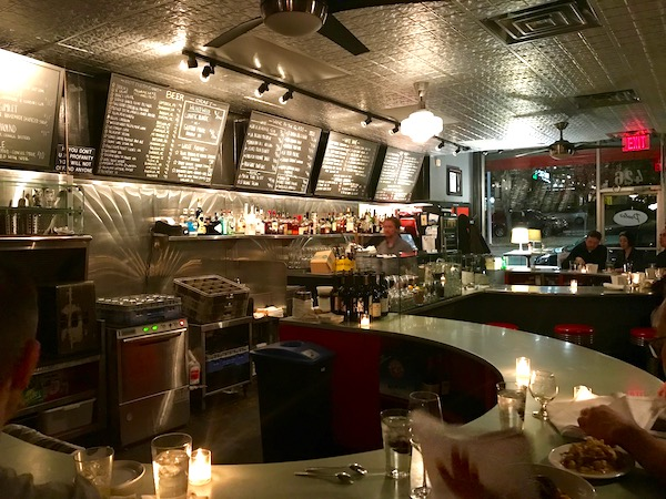A curvy bar with a chalkboard menu above it