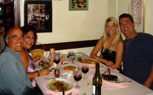 two couples seated in a restaurant with dinner on the table