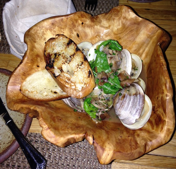 A free form olive wood bowl filled with clams, broth and slices of toasted baguette.