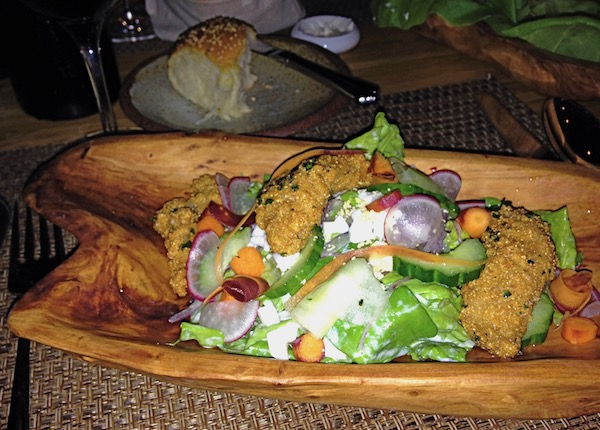 Bibb Lettuces with Cornmeal Fried Oysters in a shallow olive wood platter