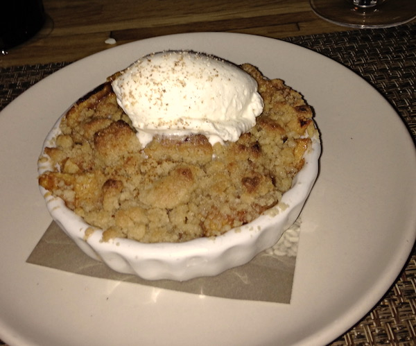 A white bowl filled with the crumb topping of an apple cobbler topped with a quenelle of vanilla ice cream.
