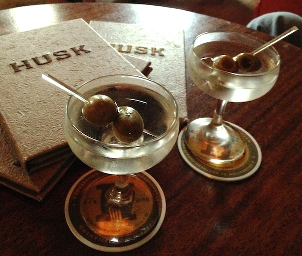 A wood table with 2 Husk menus and 2 martinis with olives