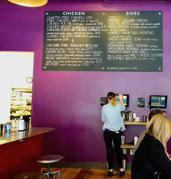 A chalkboard menu in a restaurant with purple wall.