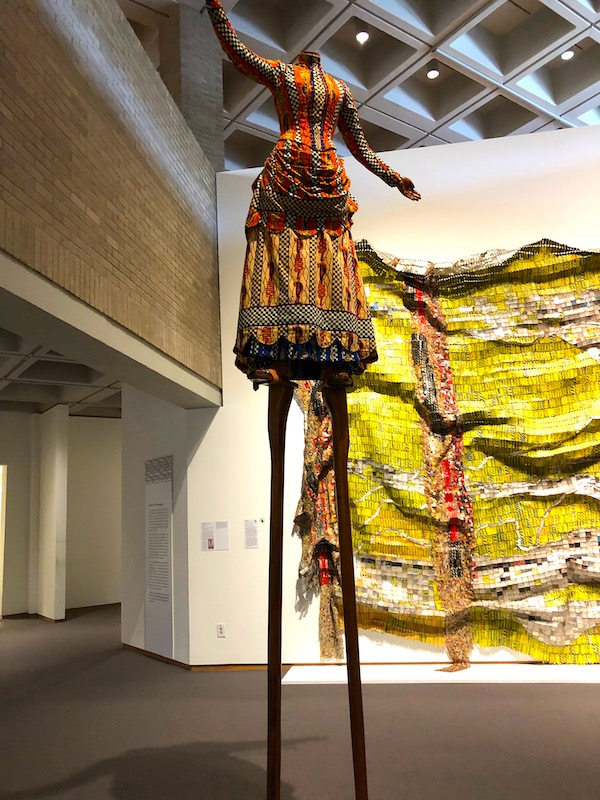 An African Dress of Hand Woven Fabric on very long legs with wall hanging in background