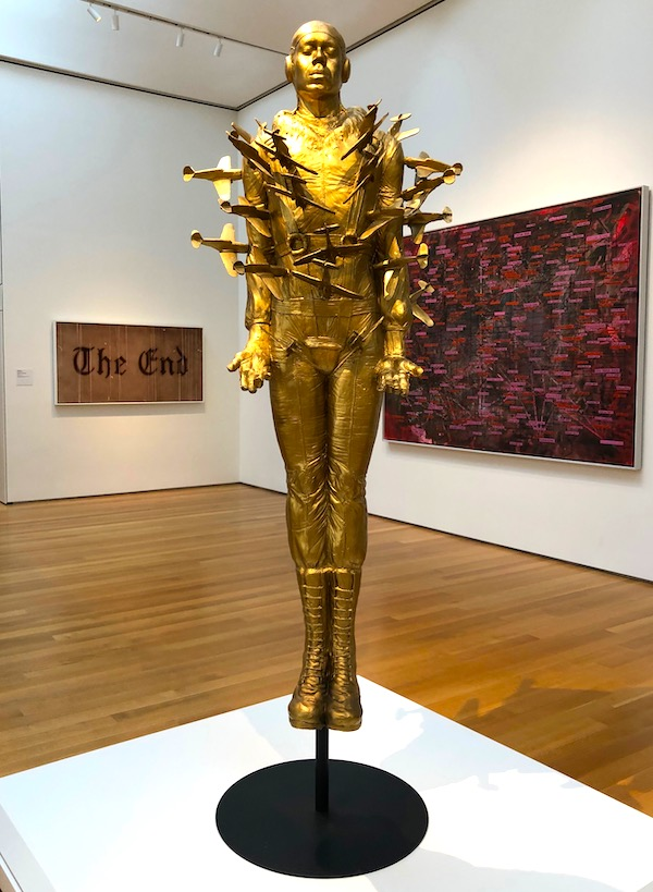 A gold sculpture of a man with small airplanes crashing into him